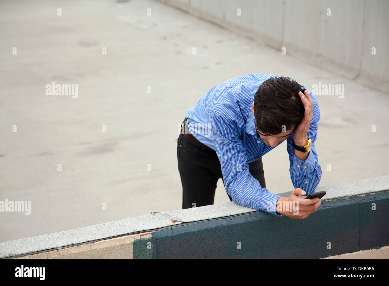 Anxious young man leaning on wall on city rooftop - Stock Image