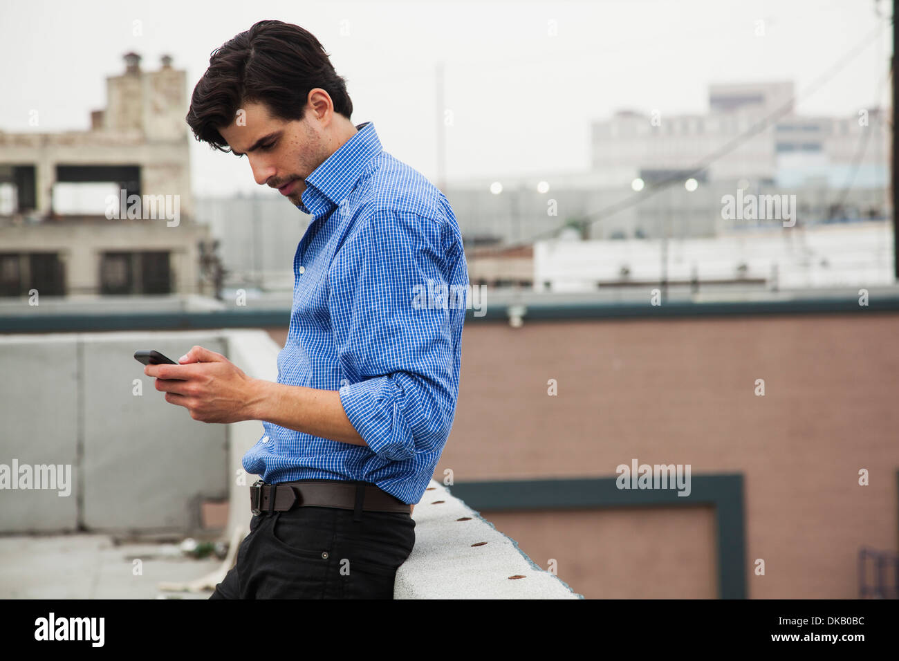 Anxious young man on city rooftop - Stock Image