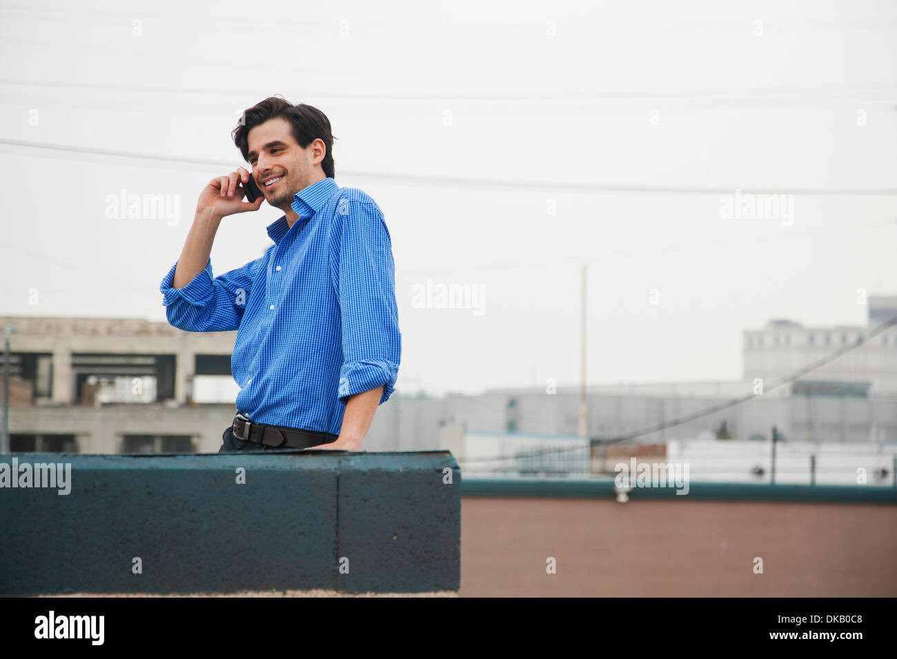 Confident young man using mobile on city rooftop - Stock Image