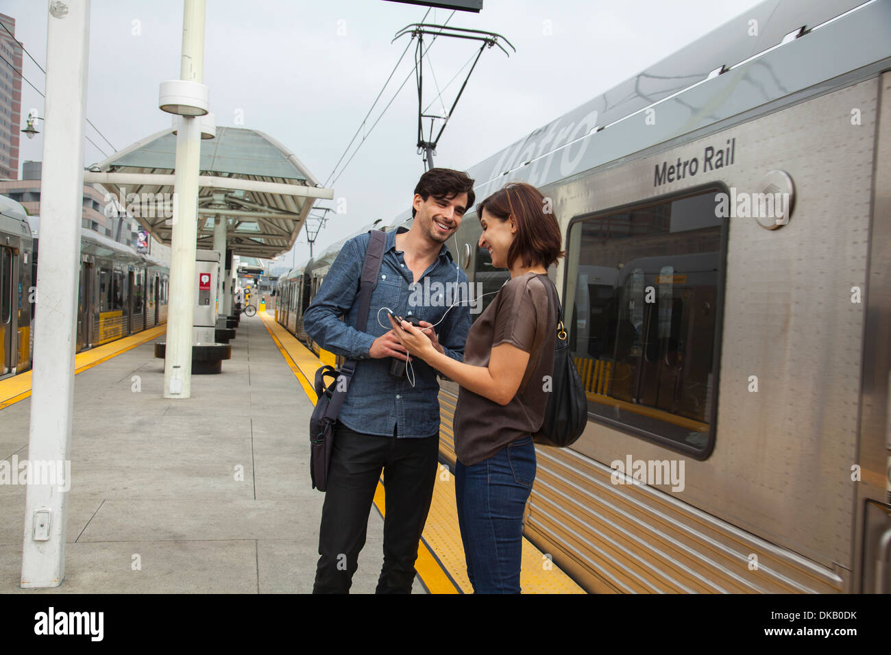 Couple listening to shared earphones at station, Los Angeles, California, USA Stock Photo