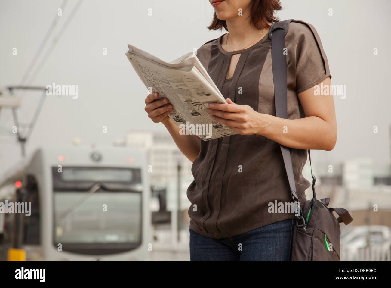 Commuter reading newspaper whilst waiting at station, Los Angeles, California, USA - Stock Image