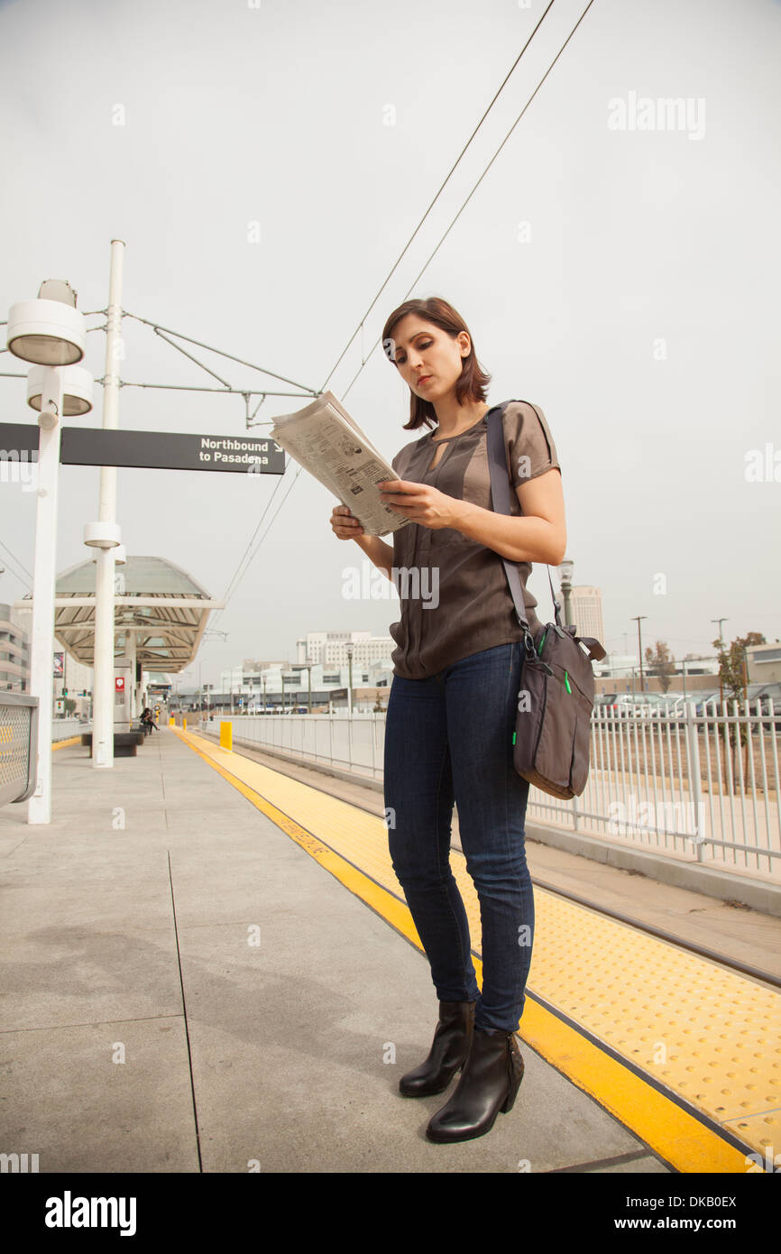 Woman reading newspaper whilst waiting at station, Los Angeles, California, USA - Stock Image