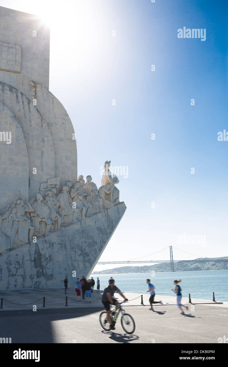 Man cycles past the Monument to the Discoveries, Belem, Lisbon, Portugal - Stock Image