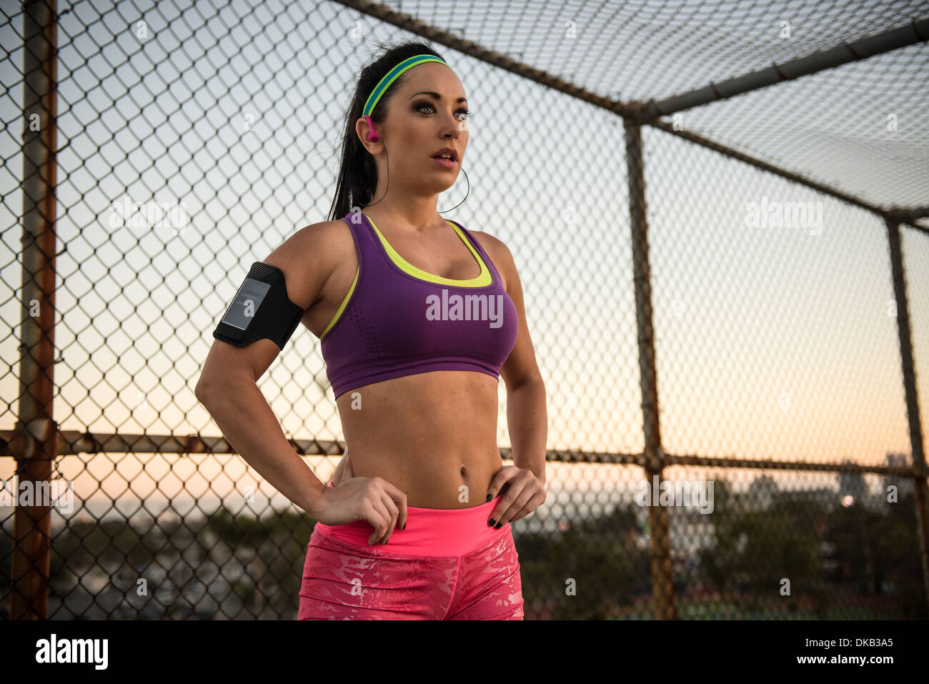 Female runner with hands on hips listening to mp3 player - Stock Image