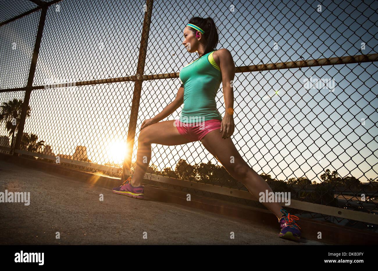 Female runner stretching on walkway Stock Photo