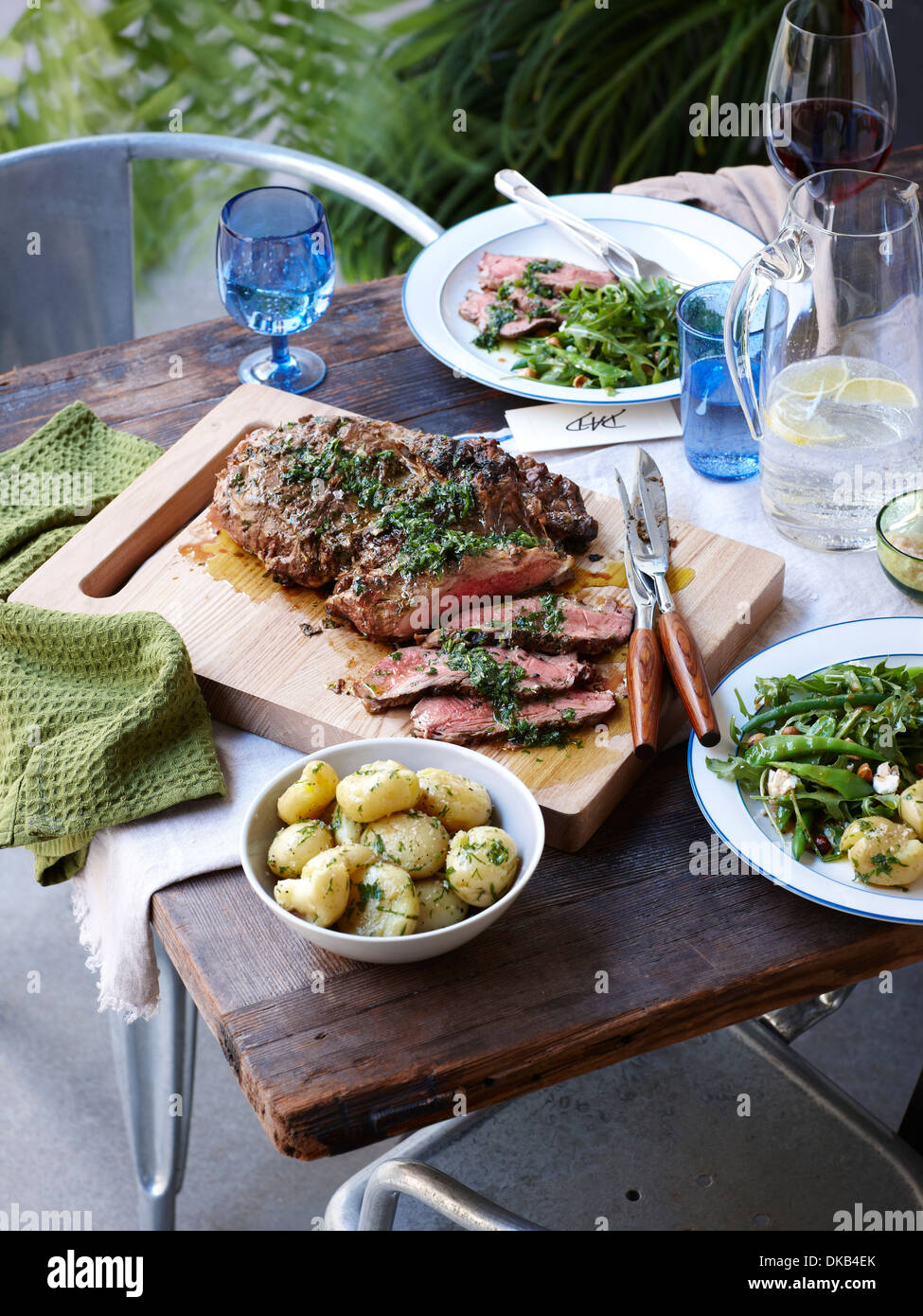 Dinner table with barbecued herb crust lamb and spring greens - Stock Image