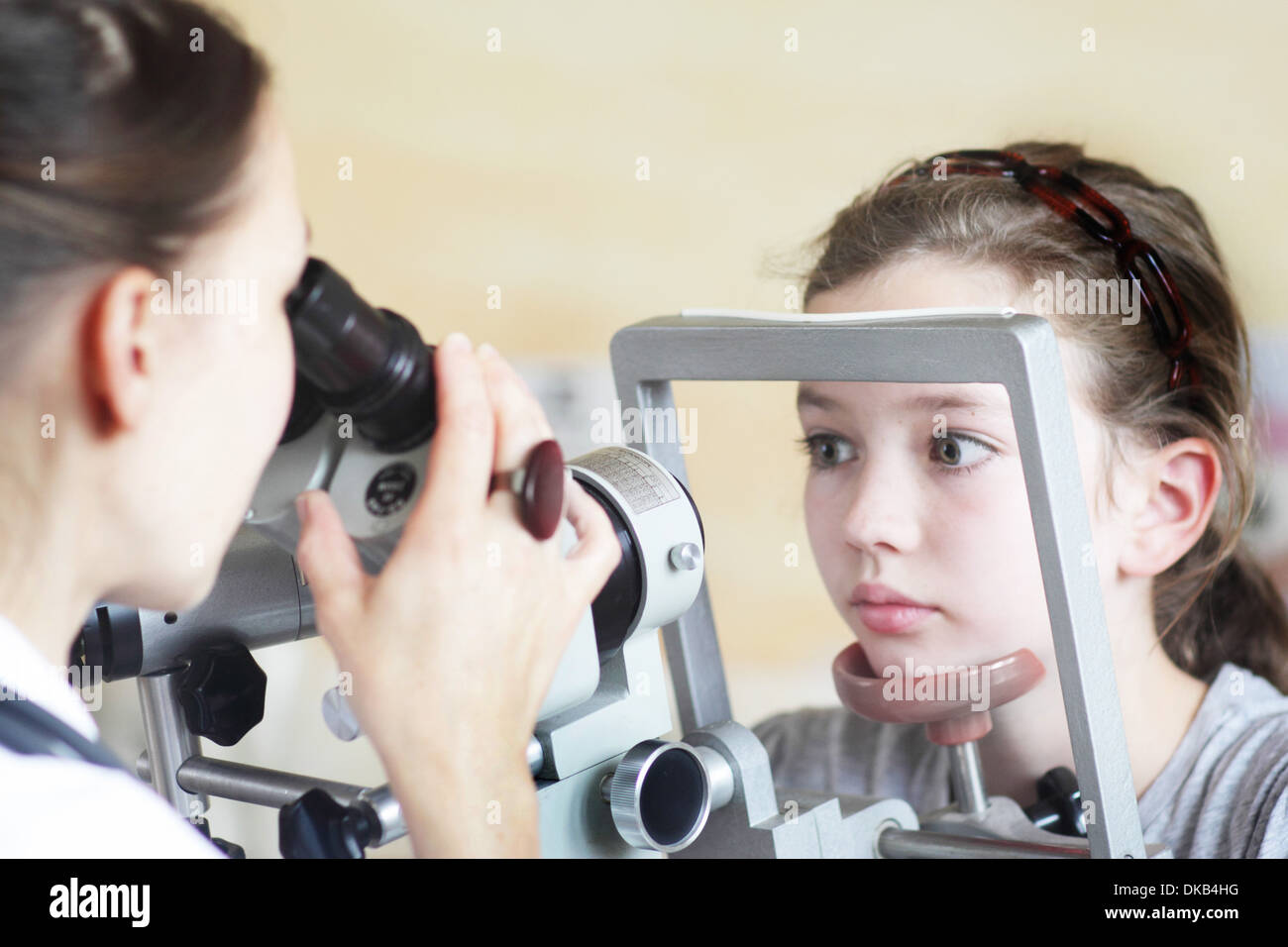 Optometrist examining girl's eyes - Stock Image