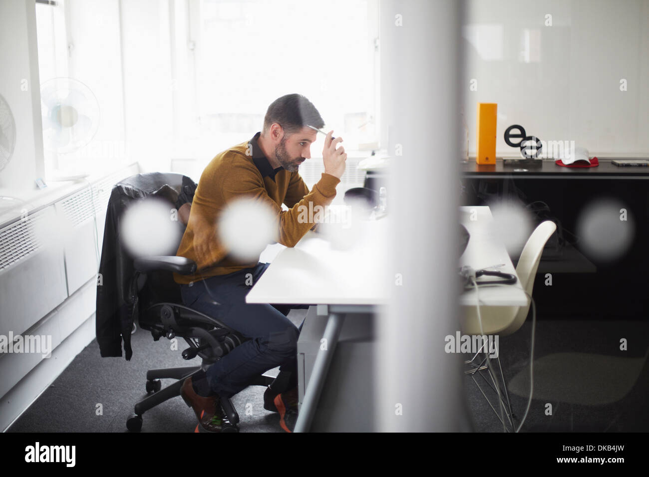 Casual businessman working at desk - Stock Image