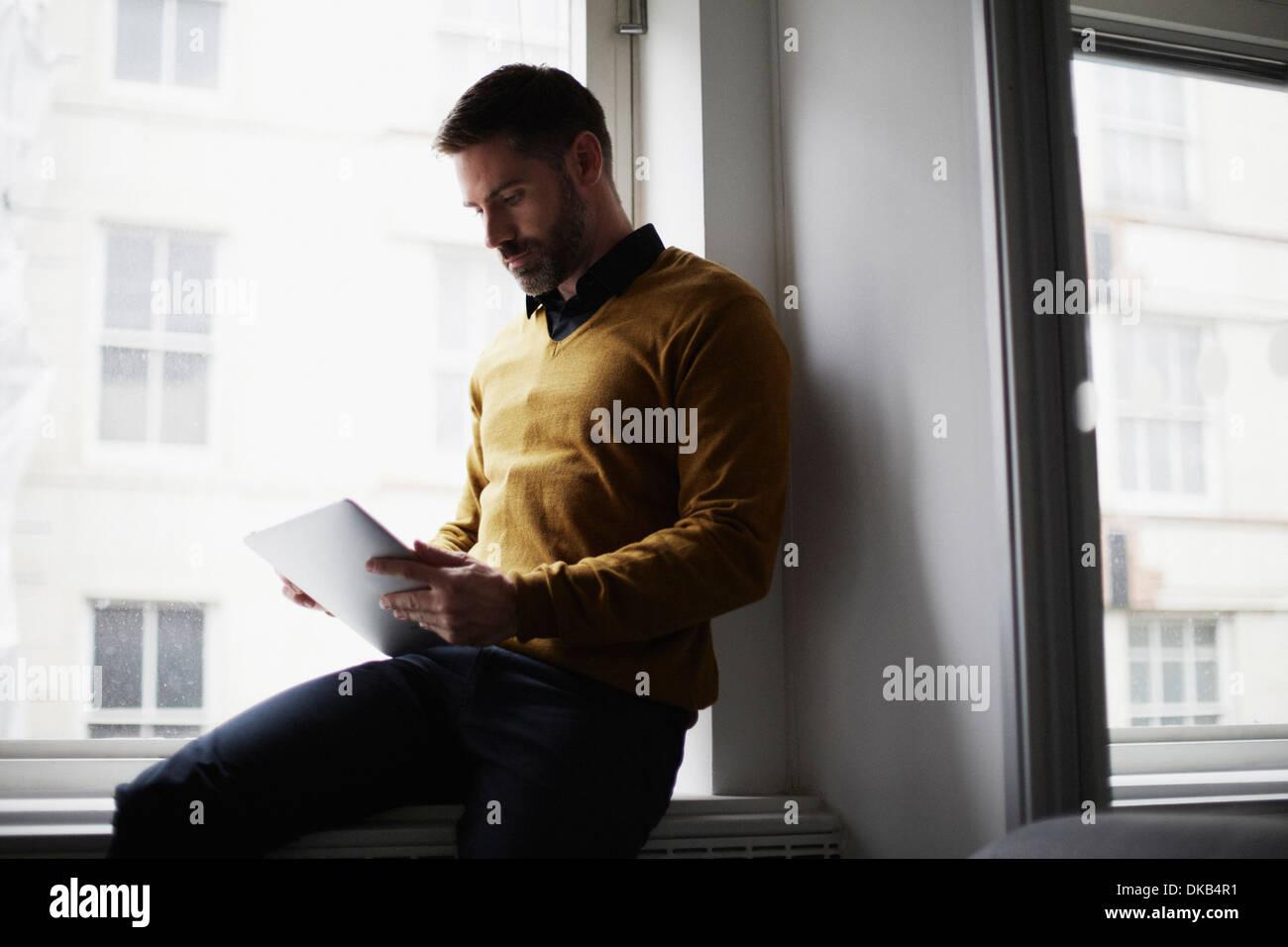 Casual businessman sitting on windowsill using digital tablet - Stock Image