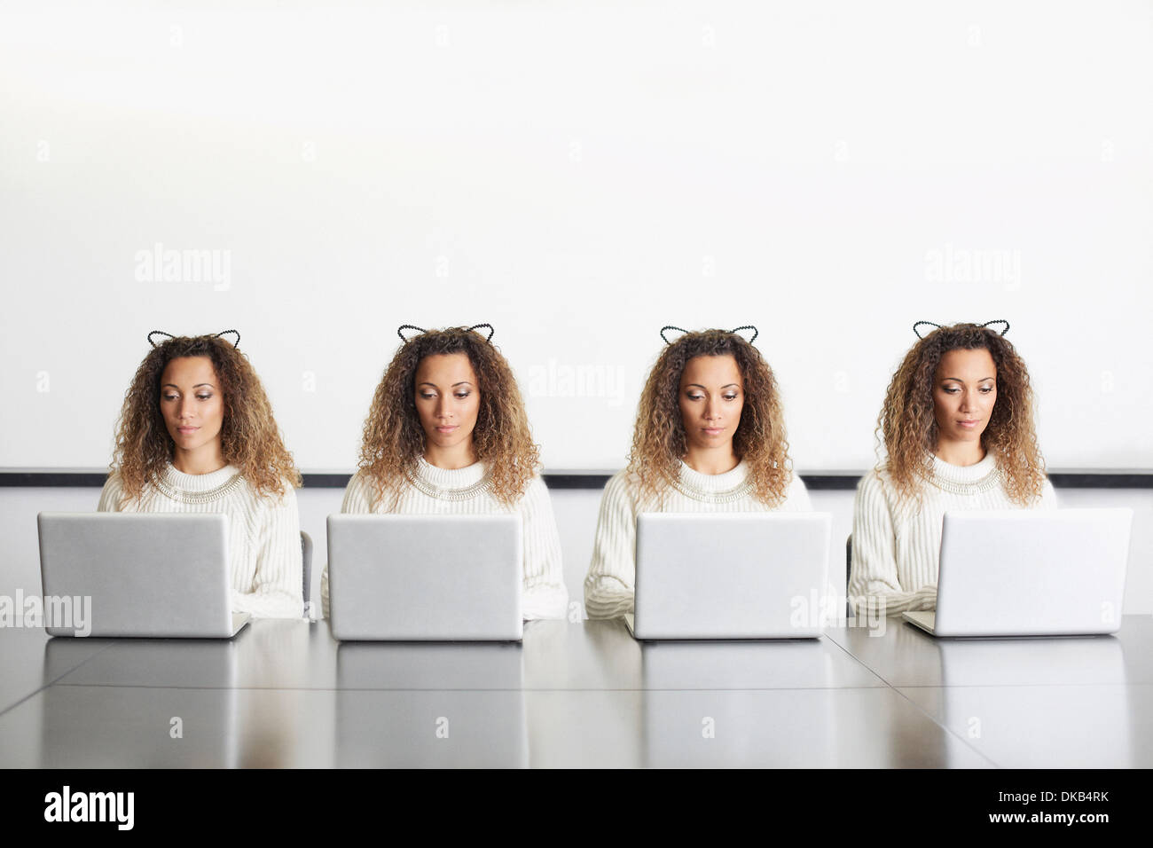 Businesswomen wearing ears using laptops - Stock Image