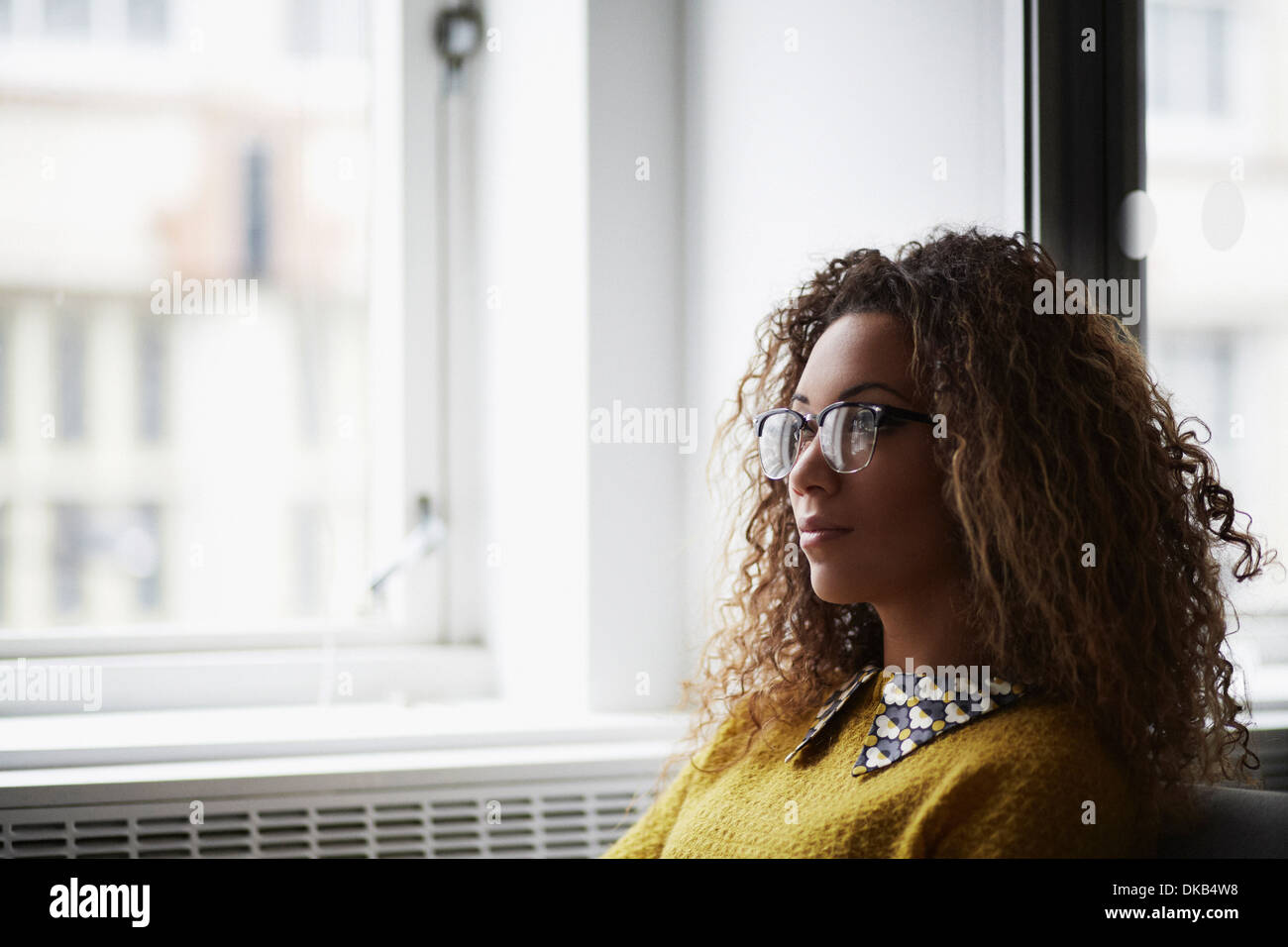 Portrait of female office worker wearing glasses - Stock Image