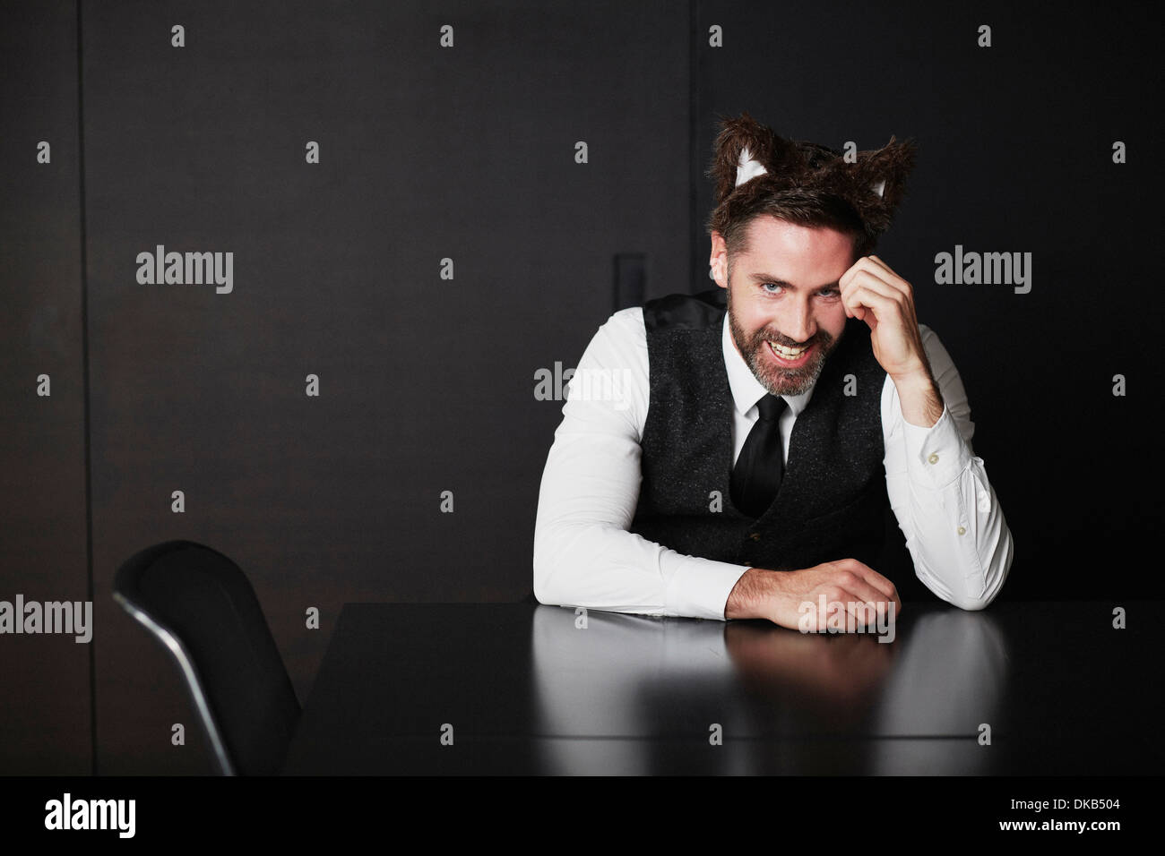 Businessman wearing animal ears - Stock Image