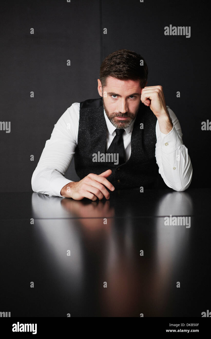 Businessman wearing waistcoat and shirt leaning on elbow - Stock Image