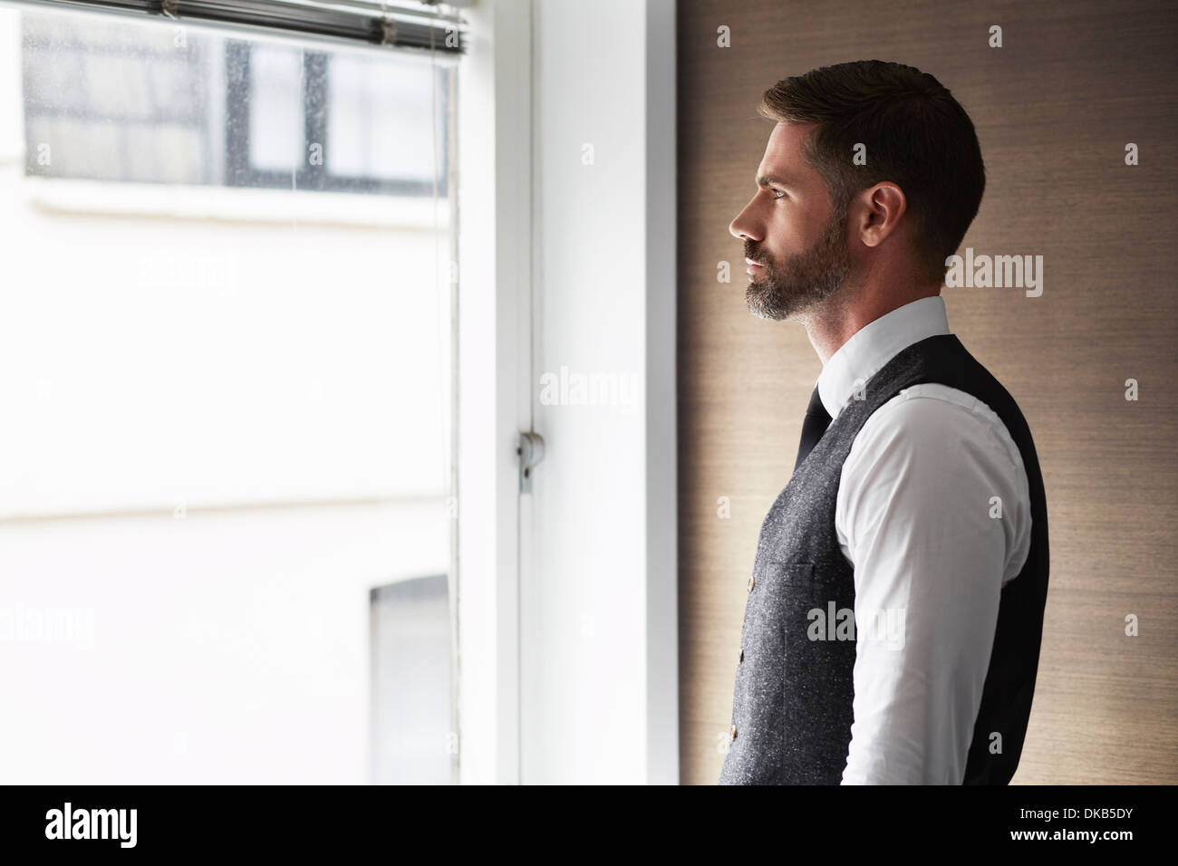 Portrait of businessman looking out of window - Stock Image