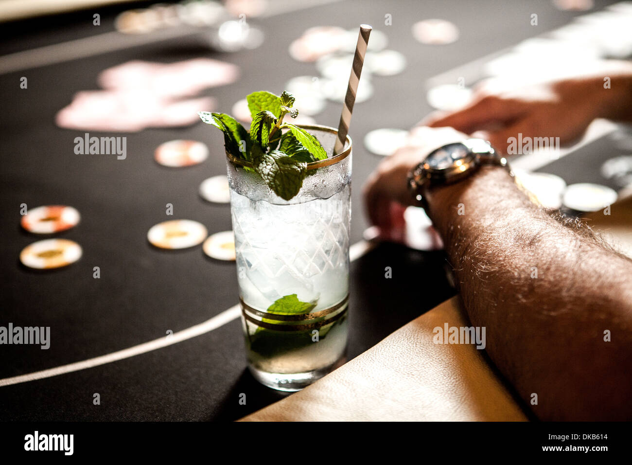 Cropped image of gambling table with playing cards, chips and cocktails - Stock Image