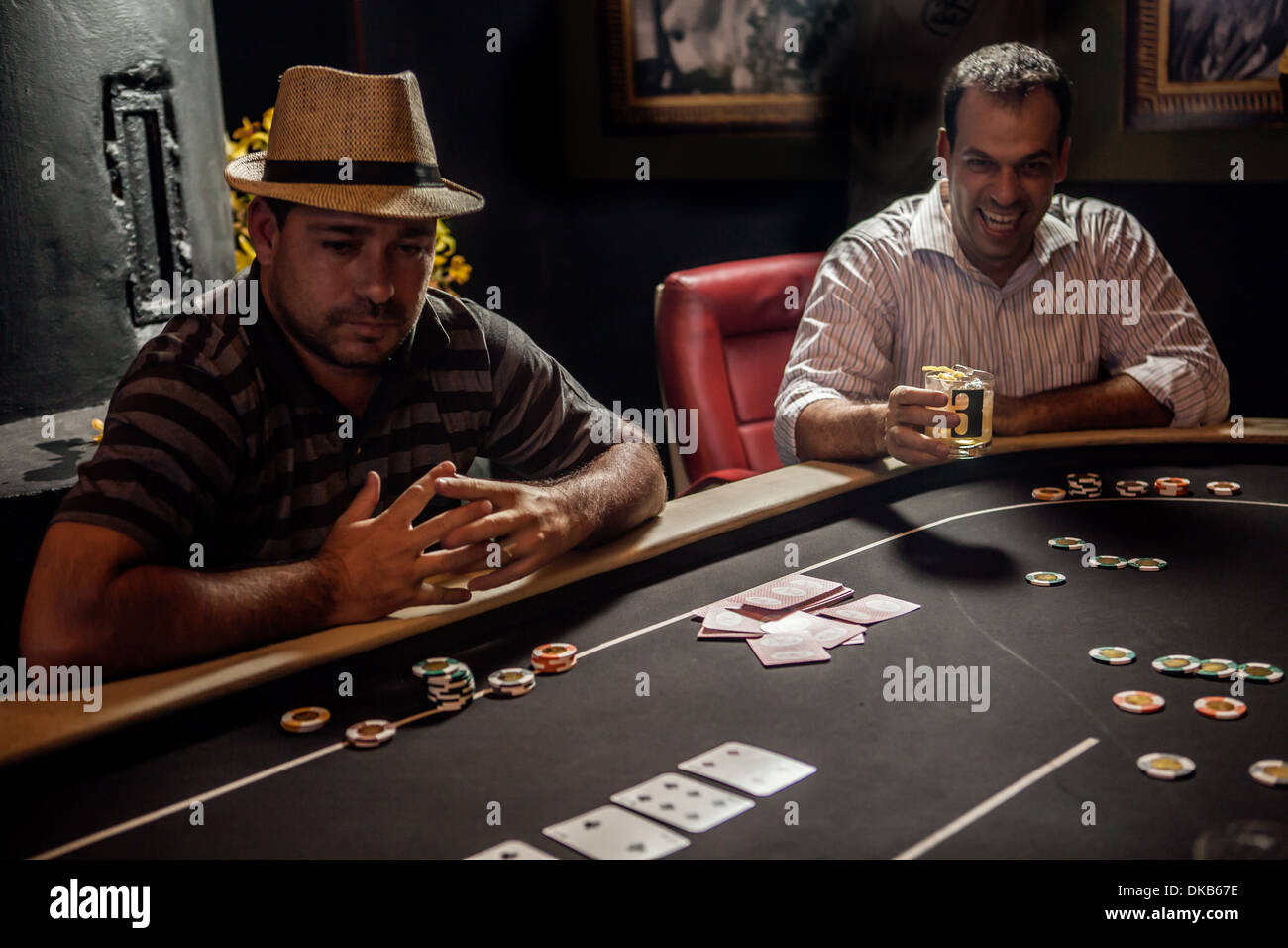 Mid adult men playing poker and drinking cocktails - Stock Image