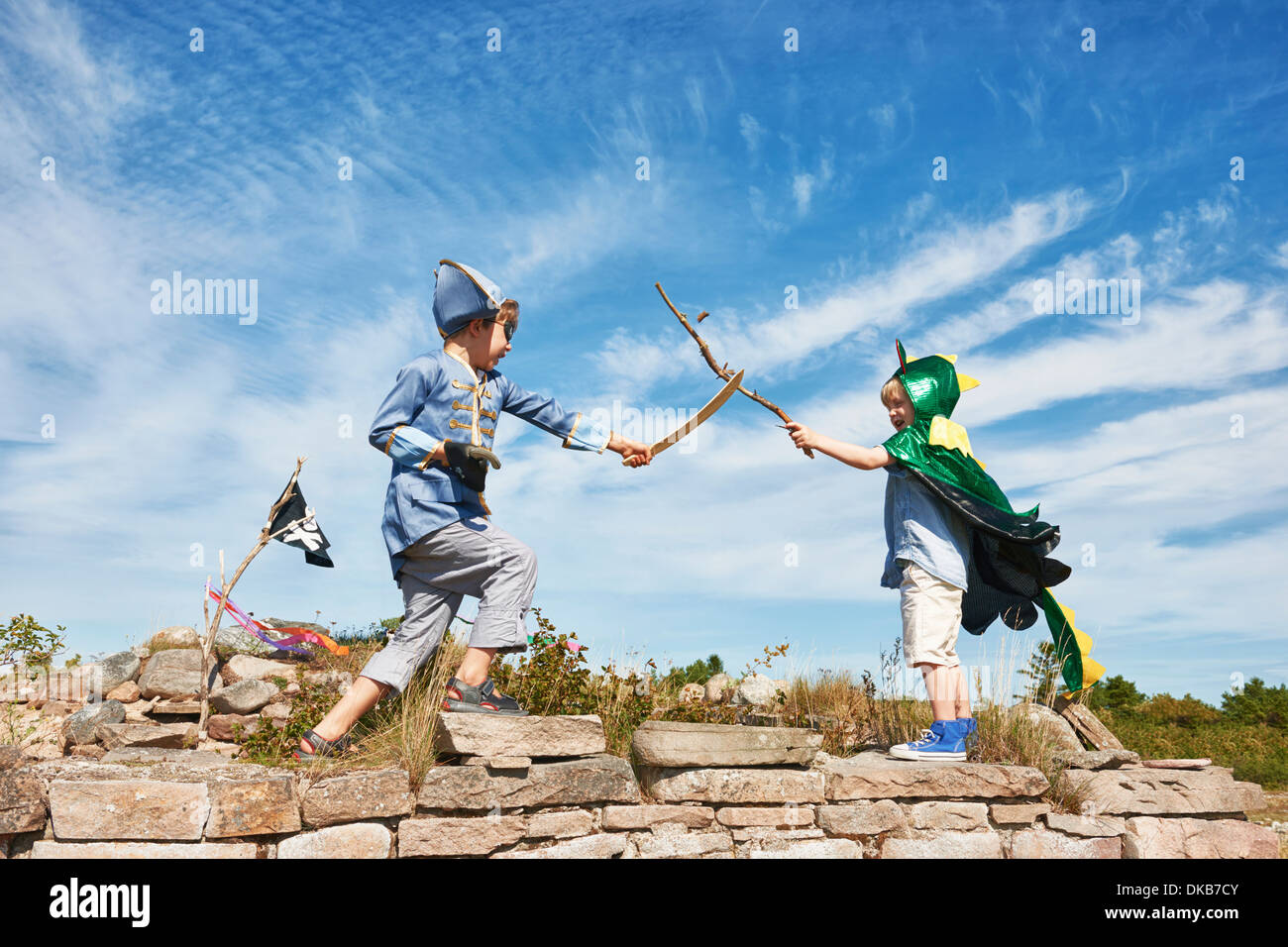 Two boys in fancy dress play fighting with sticks, Eggergrund, Sweden - Stock Image