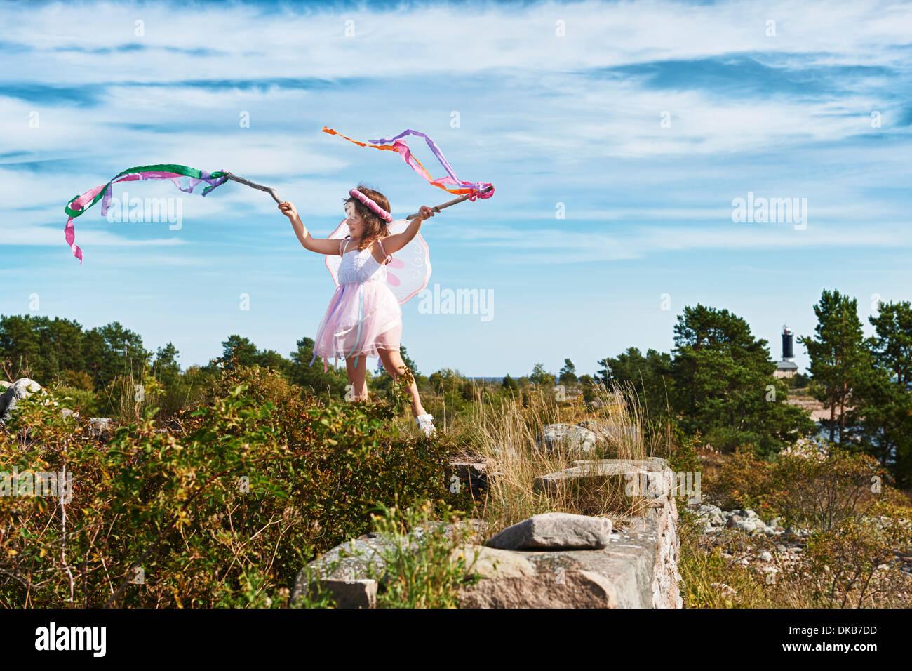 Girl in fancy dress holding streamers, Eggergrund, Sweden - Stock Image