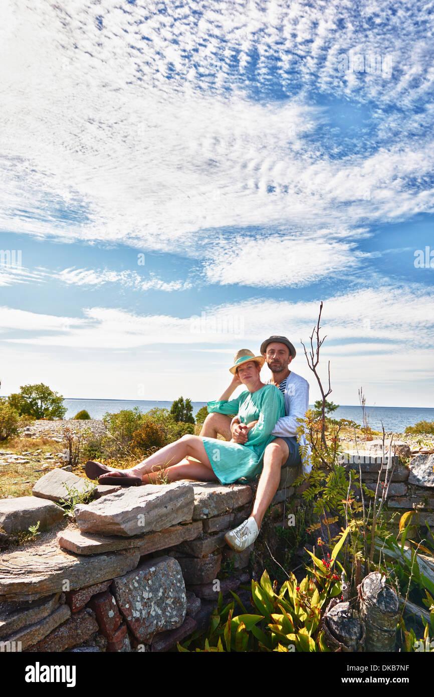 Couple sitting on stone wall, Eggergrund, Sweden - Stock Image