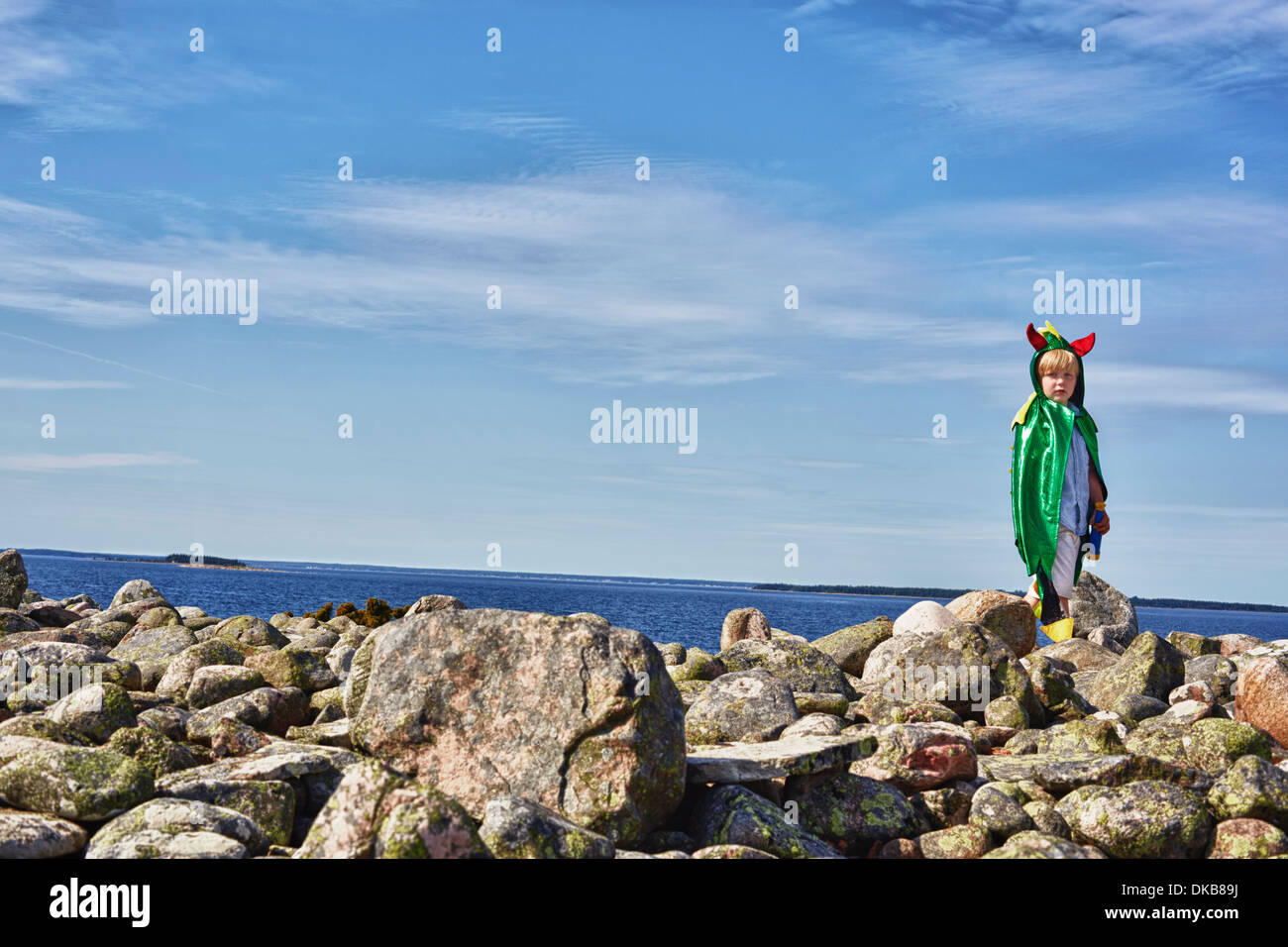 Boy wearing green cape standing on stone wall, Eggergrund, Sweden - Stock Image