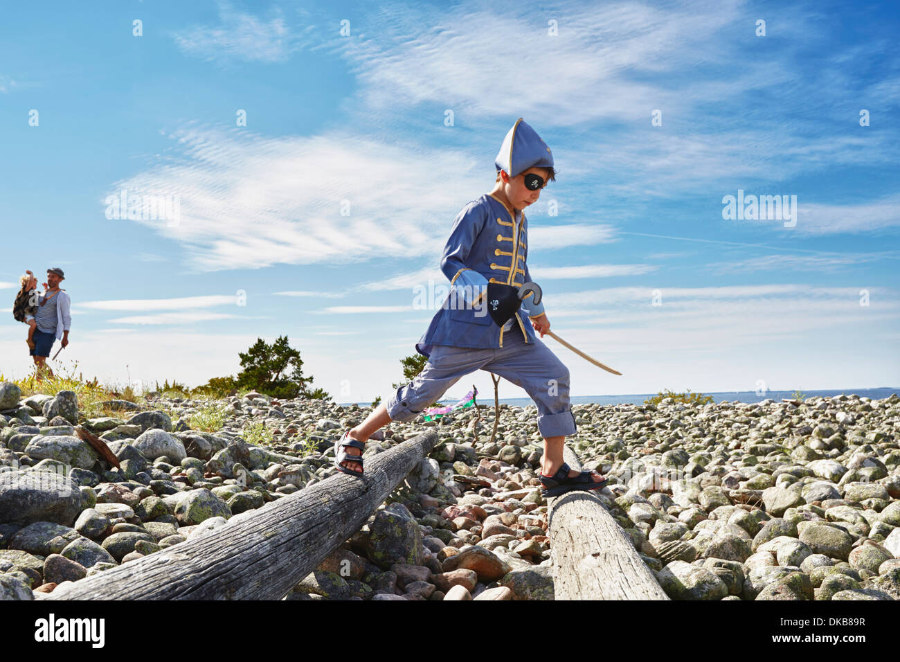 Boy dressed as pirate stepping across wooden logs on beach, Eggergrund, Sweden - Stock Image