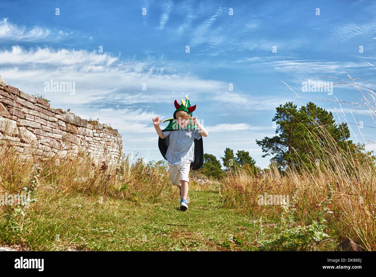 Boy wearing green cape running along grass, Eggergrund, Sweden - Stock Image