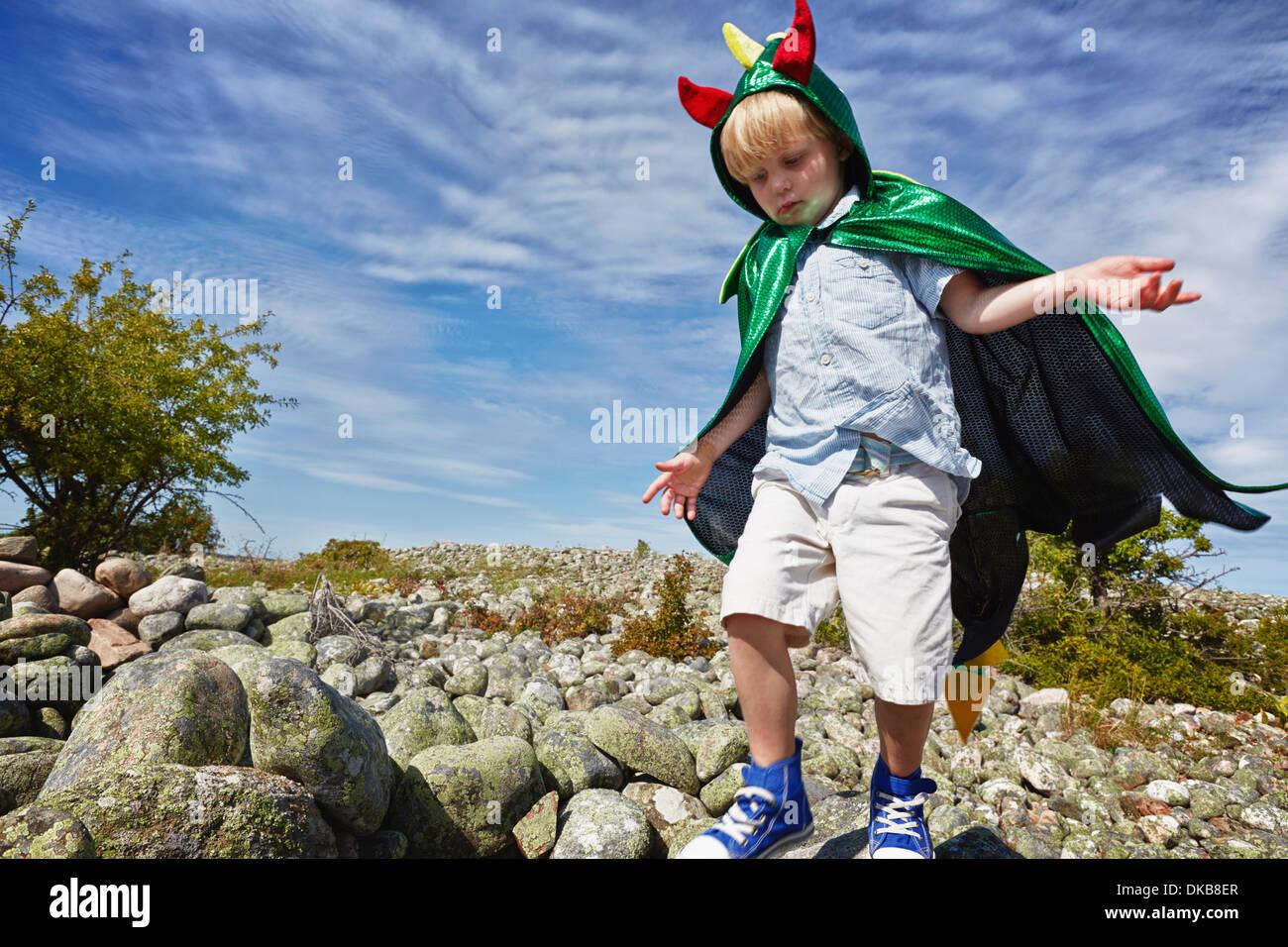Boy wearing green cape walking on pebbles, Eggergrund, Sweden - Stock Image