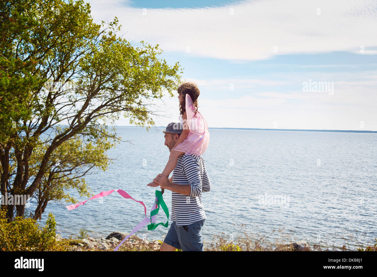 Father carrying daughter on shoulders by sea, Eggergrund, Sweden - Stock Image