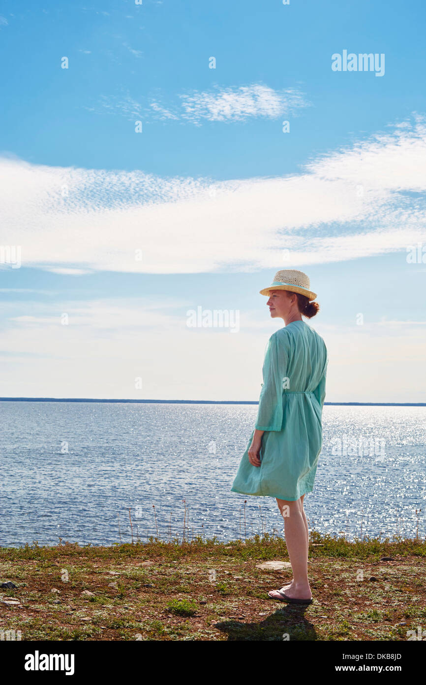 Mid adult woman standing by sea in green dress, Eggergrund, Sweden - Stock Image