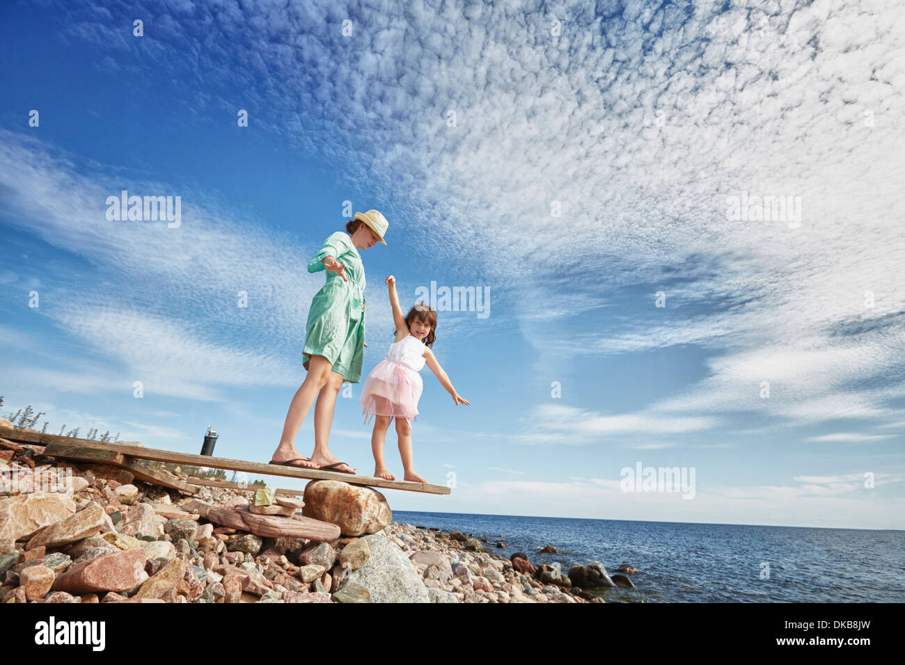Mother and daughter on wooden plank on beach, Eggergrund, Sweden - Stock Image
