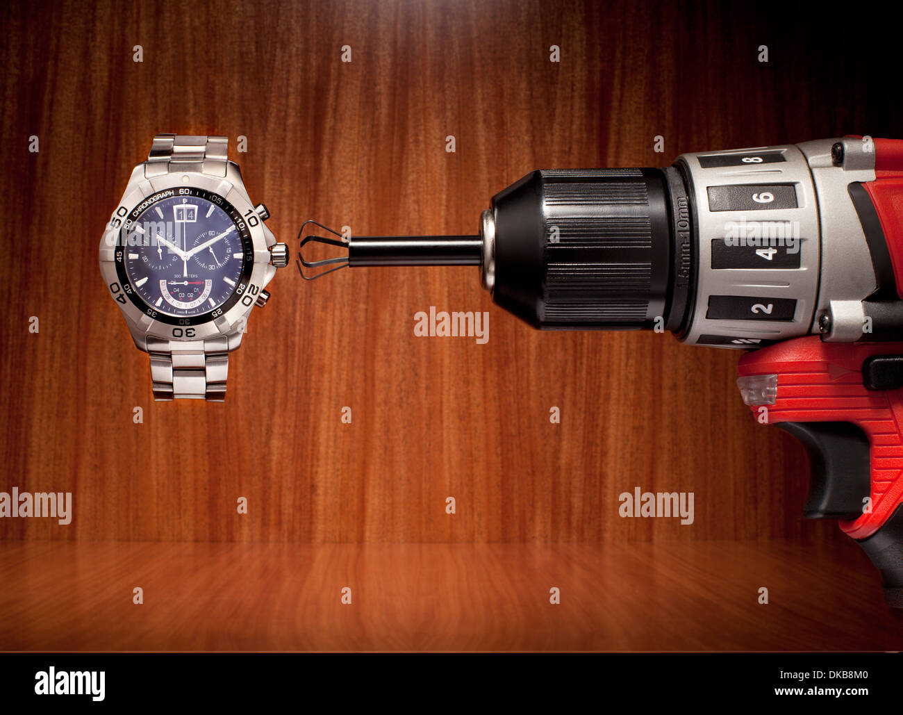 Using drill to change time on watch - Stock Image