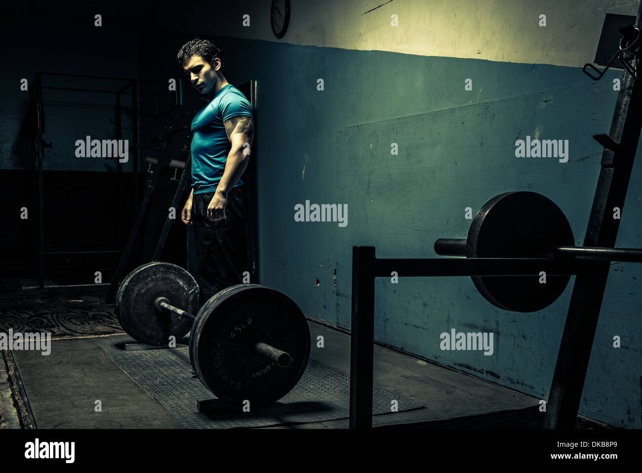 Weightlifter in dark gym, preparing to lift - Stock Image