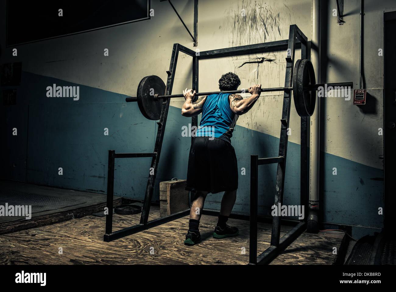 Weightlifter in dark gym - Stock Image