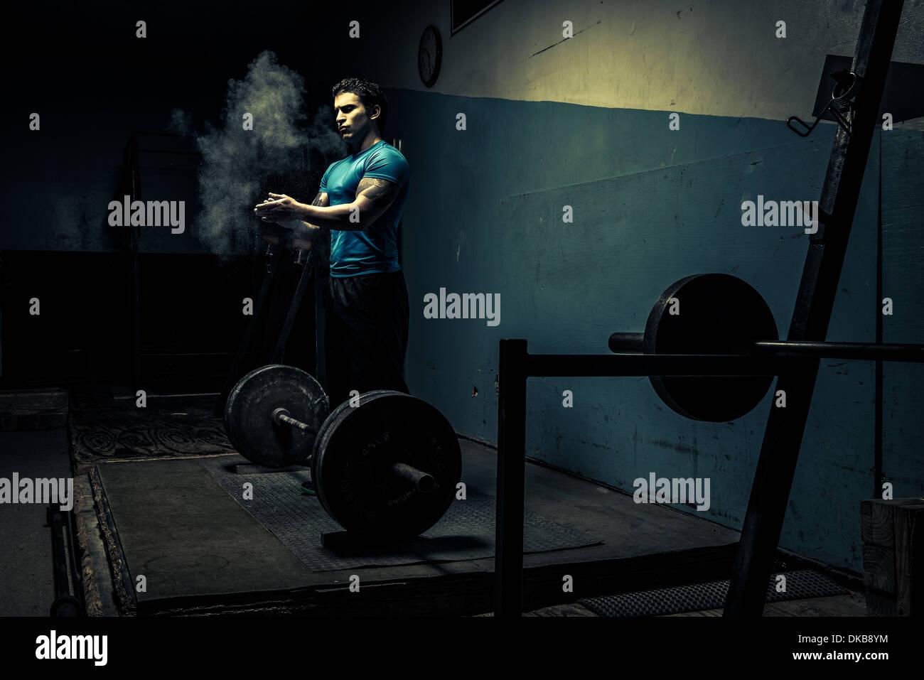 Weightlifter in dark gym, putting chalk on hands - Stock Image