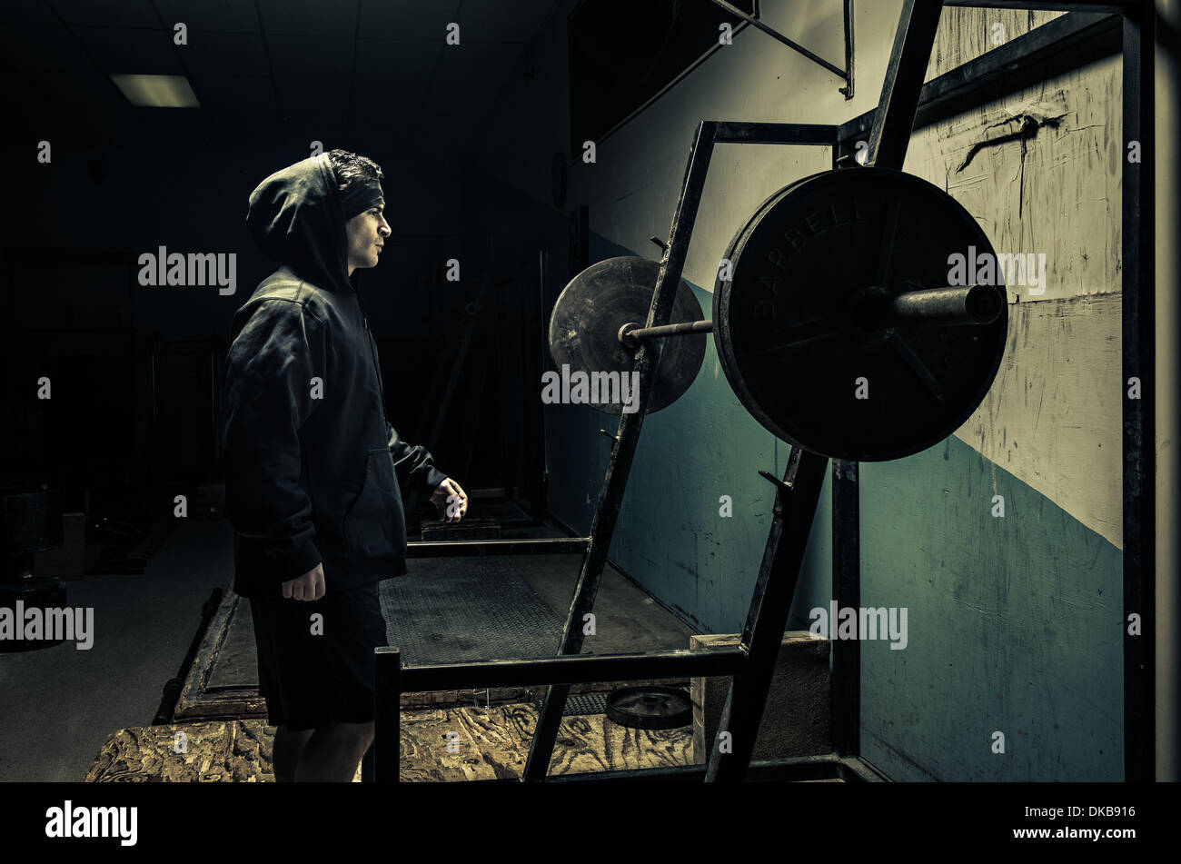 Weightlifter in dark gym - Stock Image