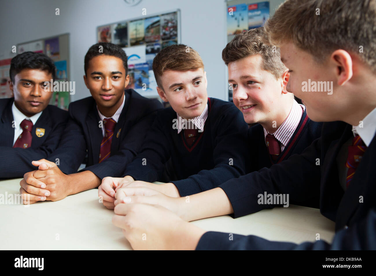 Group of schoolboys discussing ideas in class - Stock Image