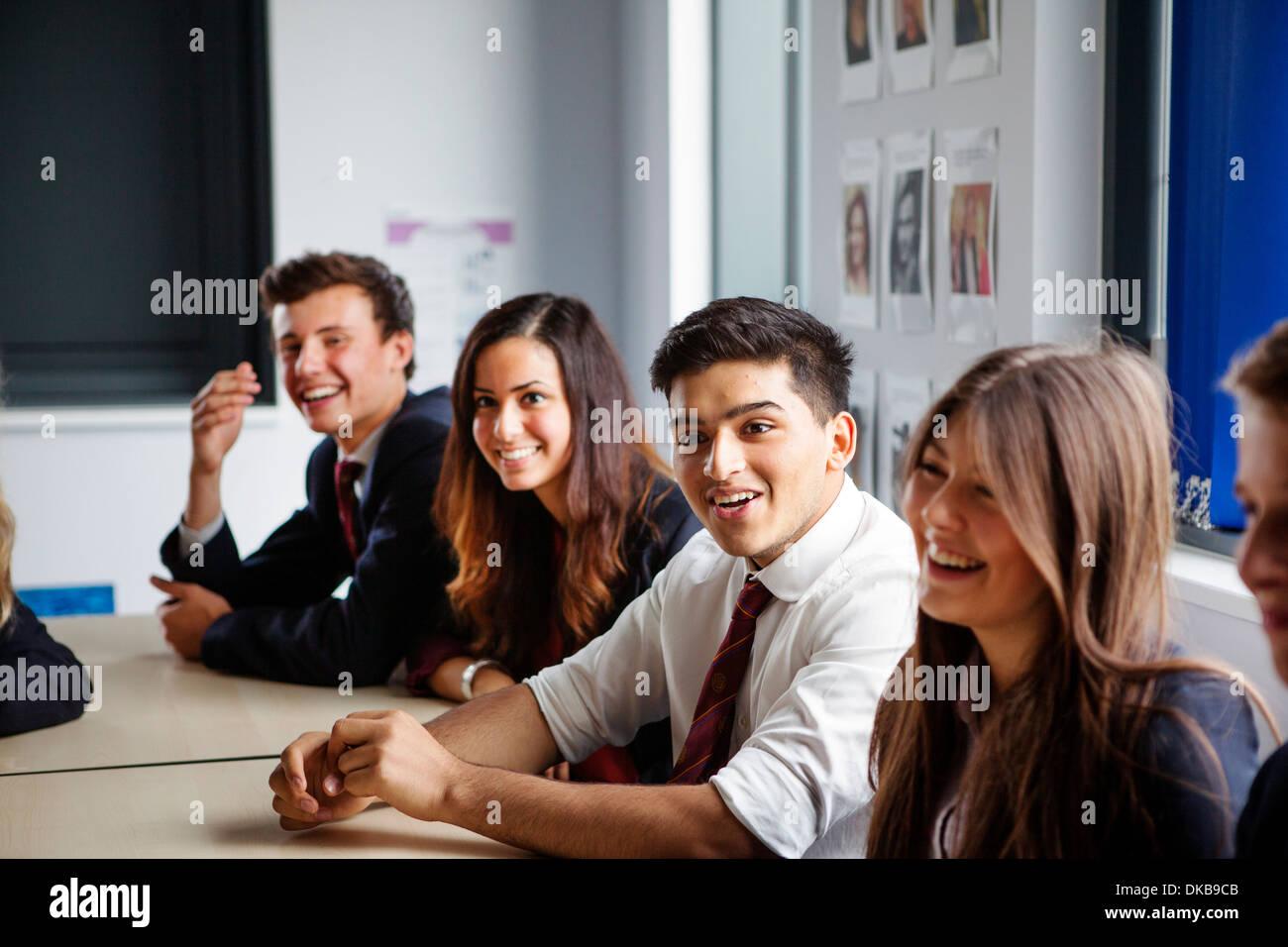 Teenage schoolchildren sitting at desks in classroom - Stock Image