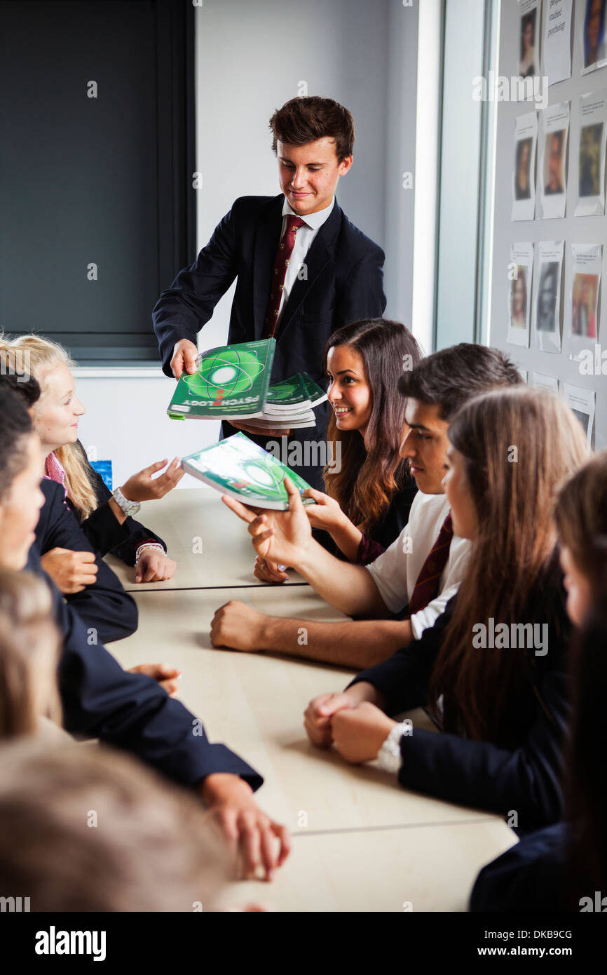 Handing out textbooks to class of teenage schoolchildren - Stock Image