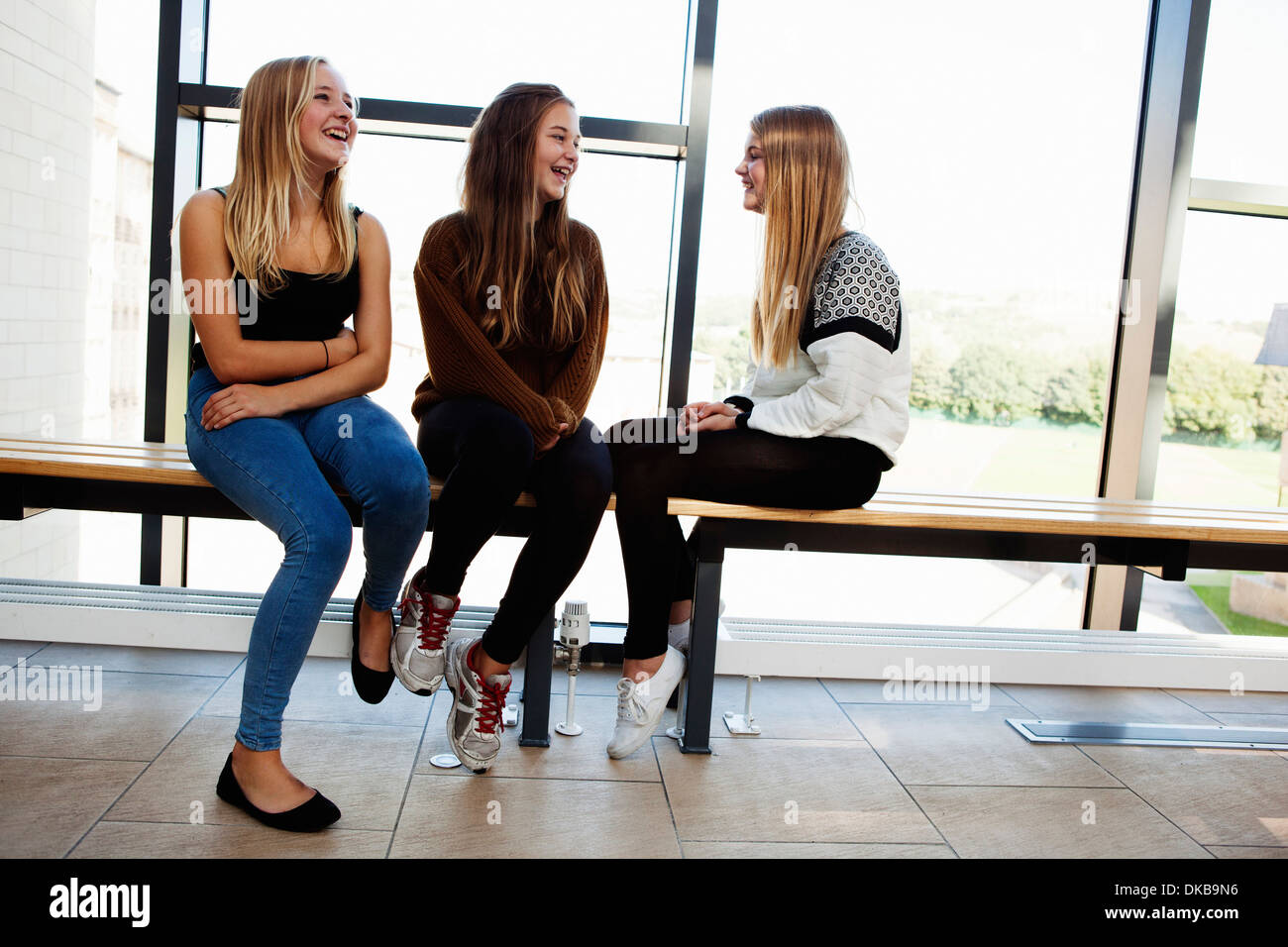 Three teenage schoolgirls sitting chatting in corridor - Stock Image