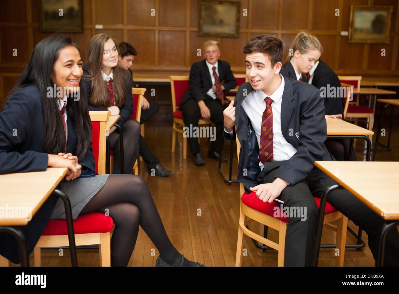 Group of  teenage schoolchildren relaxing in exam class - Stock Image