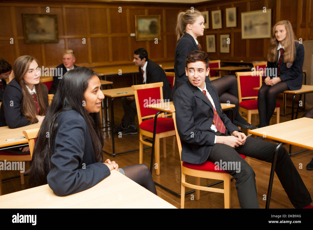 Group of  teenage schoolchildren chatting in exam class - Stock Image