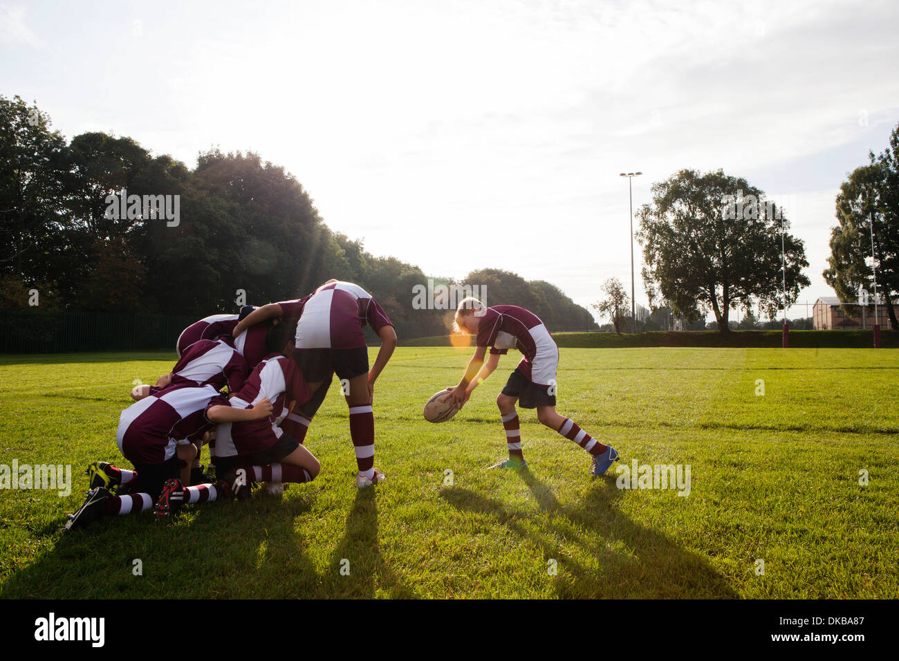 Teenage schoolboy rugby team taking ball from huddle - Stock Image
