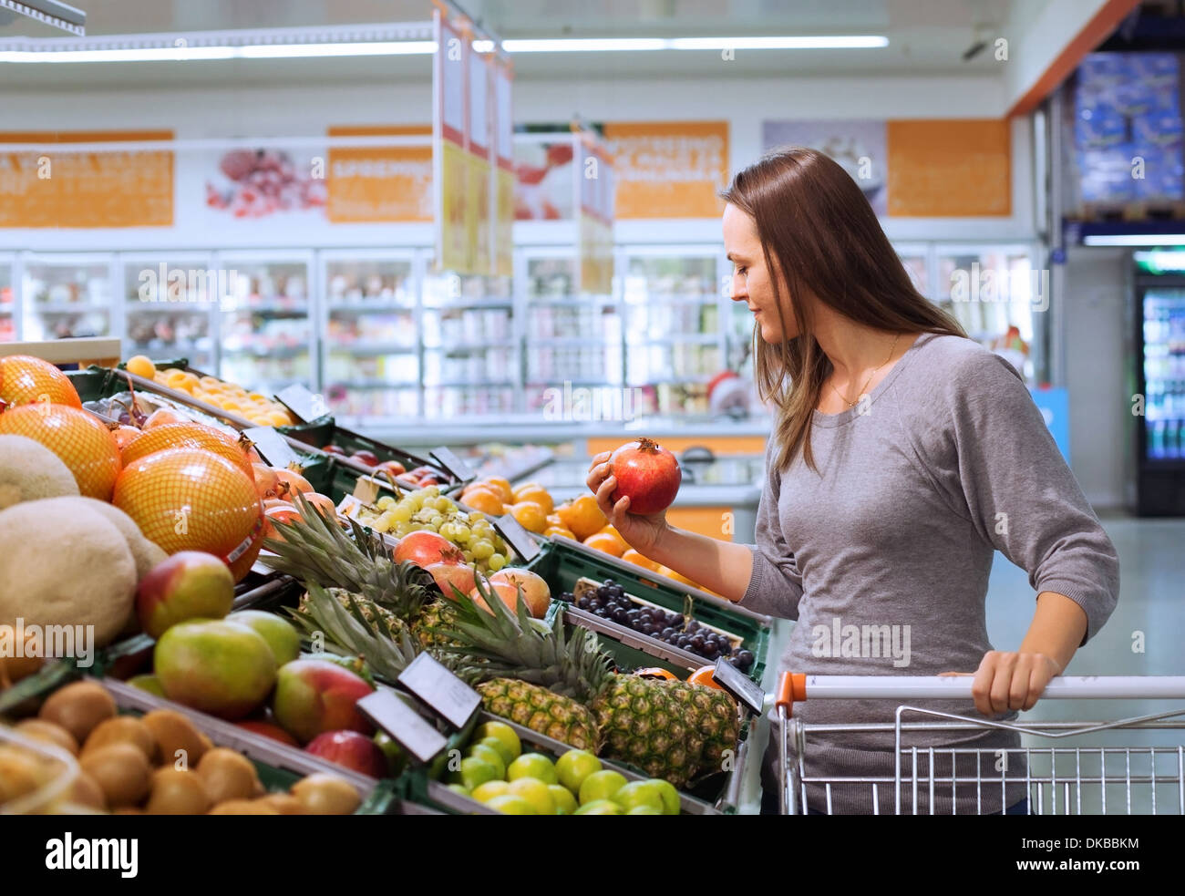 young woman in supermarket choosing fruits - Stock Image