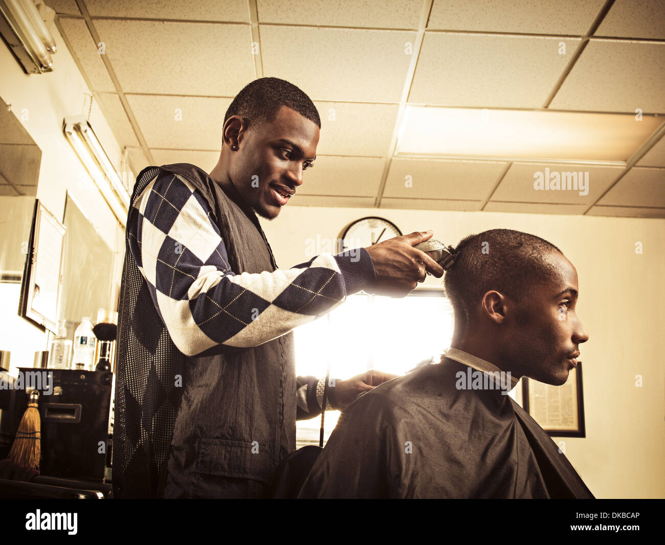 Barber in traditional barber shop shaving man's head - Stock Image