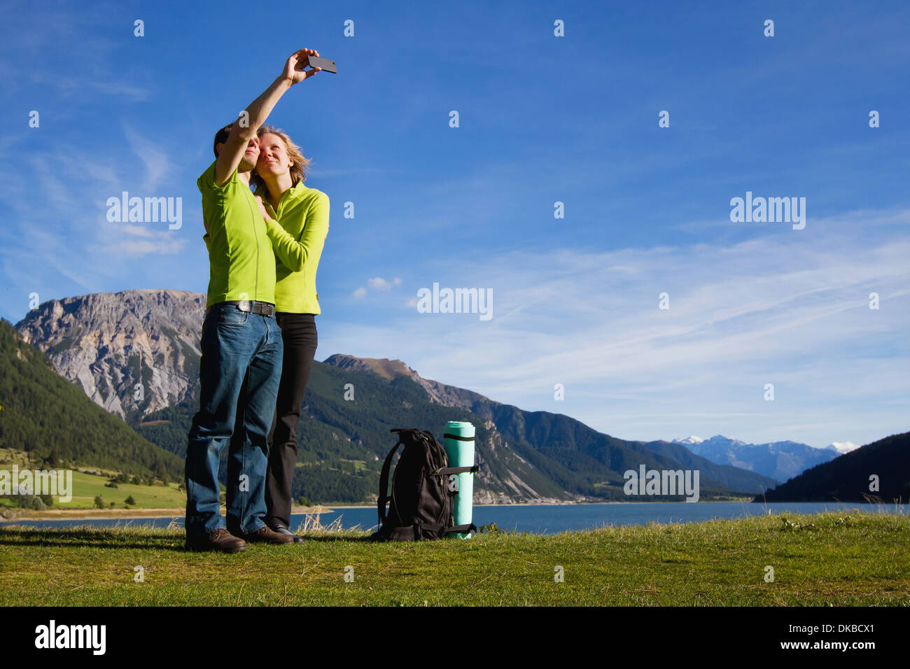 Young happy couple with backpack making photo of themselves near mountain lake - Stock Image