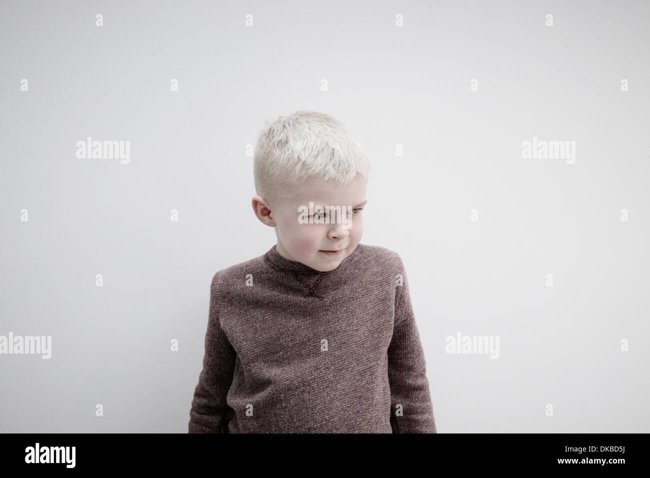 Portrait of boy wearing brown jumper, looking away - Stock Image