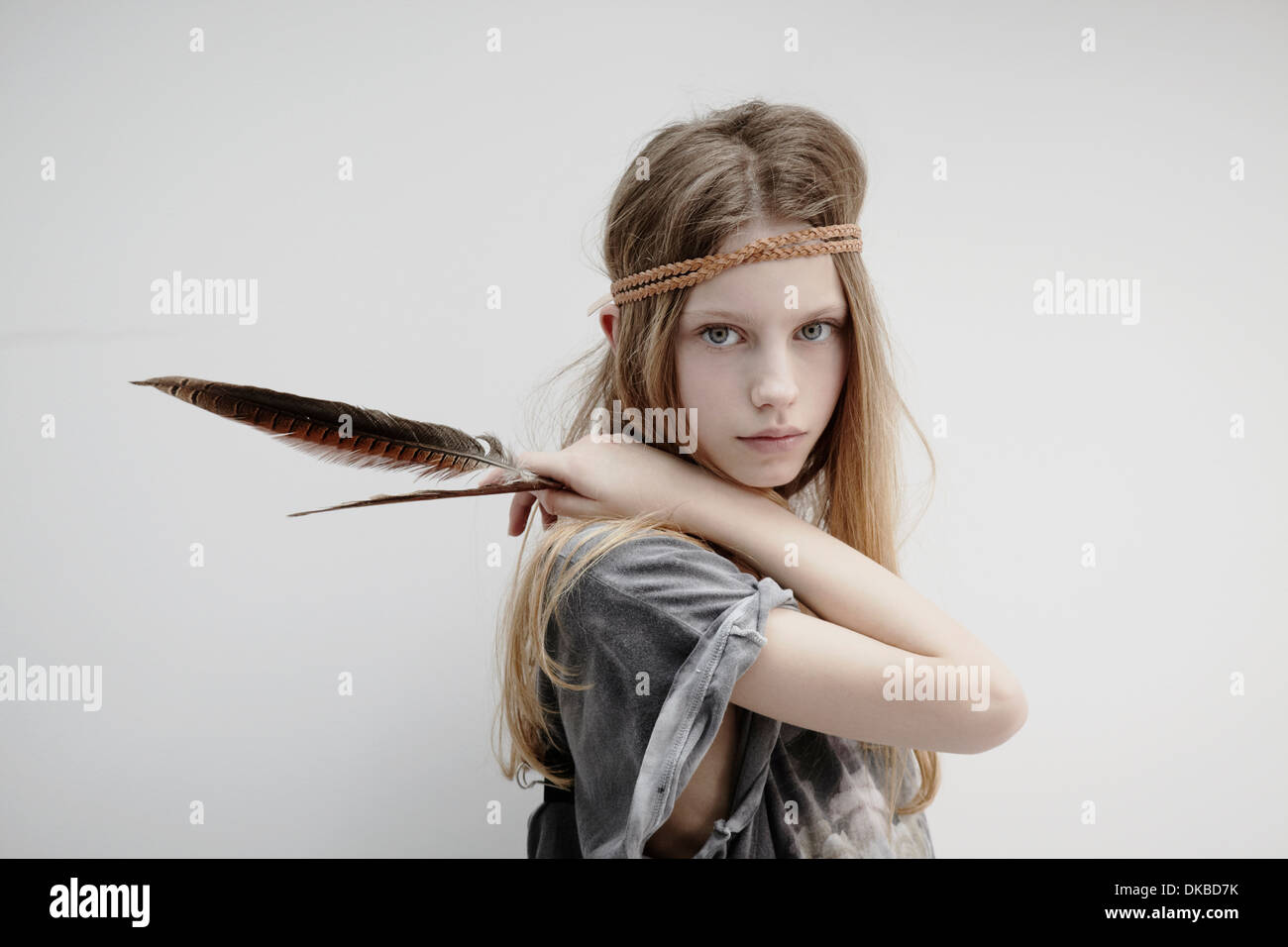 Portrait of girl wearing leather braid around head, holding feather - Stock Image