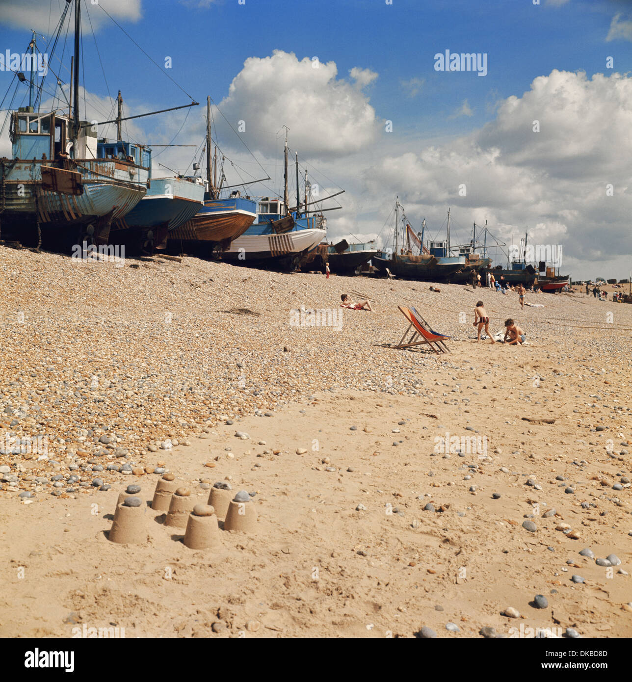 Fishing boats and children's sandcastles on Hastings Stade beach East Sussex England GB UK - Stock Image