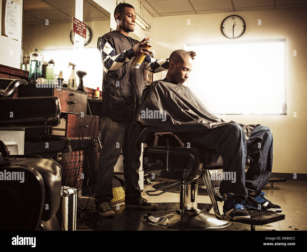 Barber in traditional barber shop spraying hairspray on man - Stock Image