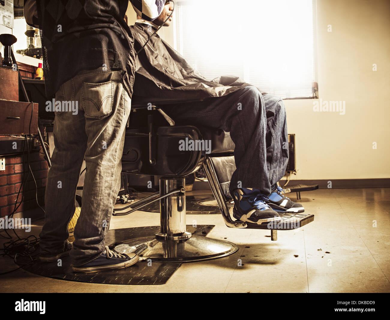Barber in traditional barber shop shaving man's head - Stock Image